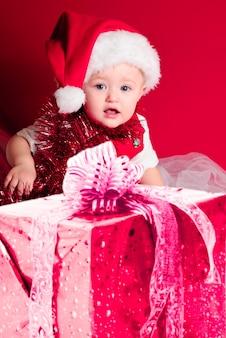Bébé en bonnet de noel sur fond rouge