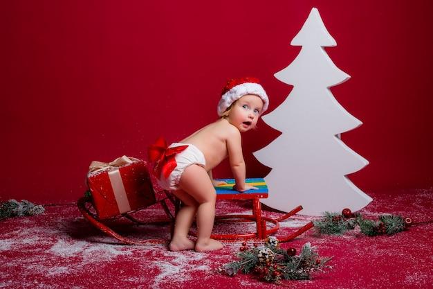 Bébé en bonnet de noel sur mur rouge