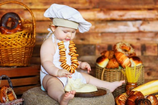 Un bébé boulanger dans un chapeau de chef et un tablier avec un tas de bagels autour du cou prépare la pâte pour la cuisson sur fond de produits de boulangerie