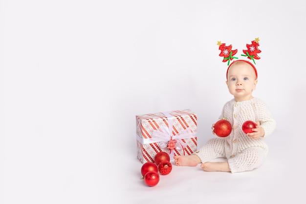Bébé avec cadeau et boules de noël sur fond isolé blanc, espace pour le texte, le nouvel an et le concept de noël