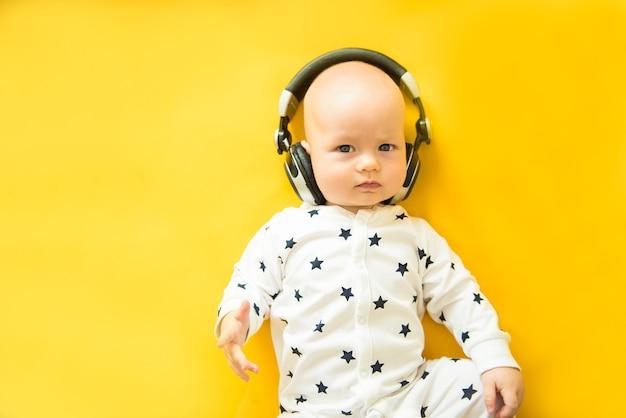 Bébé avec casque se trouve sur fond jaune