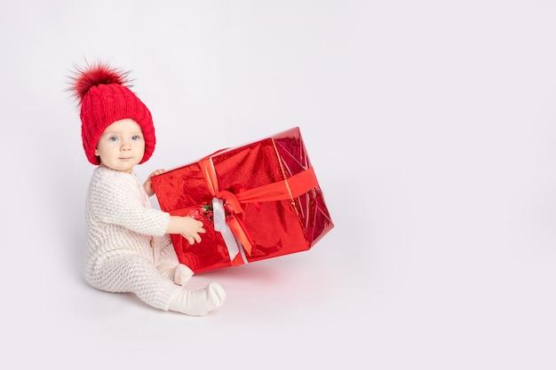 Le bébé avec le chapeau rouge et cadeau sur fond blanc isolé, espace pour le texte, concept de nouvel an et noël