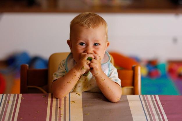 Bébé conduit le sevrage, bébé apprenant à manger avec ses premiers aliments.