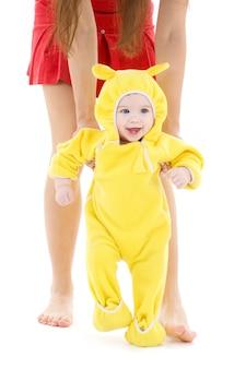 Bébé en costume jaune faisant ses premiers pas