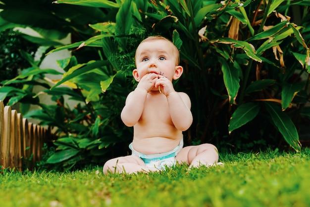 Bébé en couche sans vêtements assis sur l'herbe mordillant une fleur.
