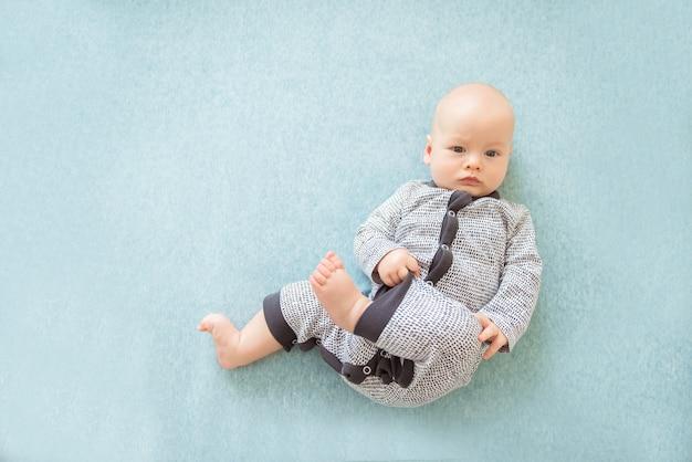 Bébé curieux calme couché sur fond bleu, regardant la caméra, vue du dessus