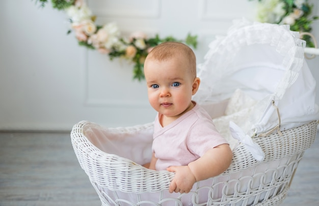 Bébé dans un body rose est assis dans une poussette rétro sur fond blanc avec des fleurs