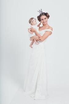 Bébé dans les bras de la mère. femme tenant un enfant. mode pour fille. reine avec princesse