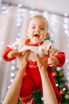 Bébé dans une combinaison de noël tricotée dans les bras de sa mère devant un arbre de noël. photo de haute qualité