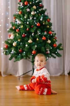 Bébé dans une combinaison rouge et blanche tricotée devant un sapin de noël. photo de haute qualité