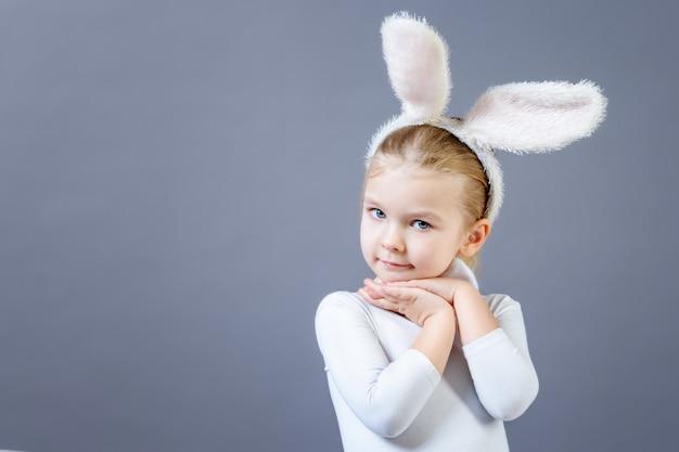 Bébé dans un costume de lapin blanc. jolie petite fille avec des oreilles de lièvre, près de l'espace de copie.