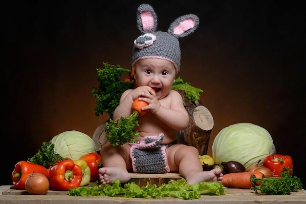 Bébé dans un costume de lapin avec des légumes sur un bois