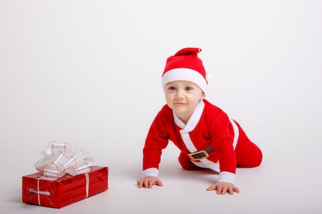 Un bébé dans un costume de père noël sur fond blanc