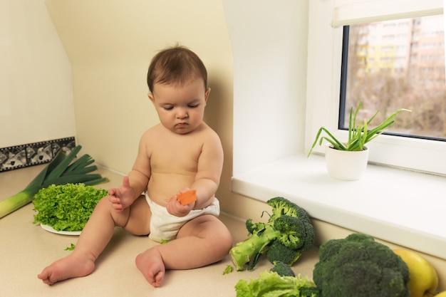 Le bébé dans la couche est assis sur la table de la cuisine. un enfant joue et s'amuse avec des fruits et légumes frais biologiques.