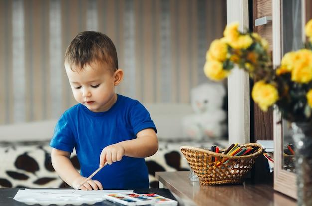 Le bébé dans la crèche, sur la table noire dans la chemise bleue, avec enthousiasme dessine des peintures