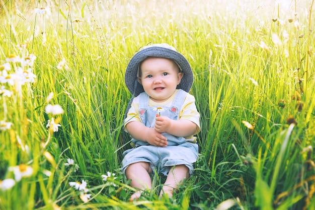 Bébé dans la nature la plus mignonne petite fille souriante dans l'herbe verte avec des fleurs en été