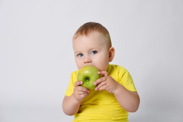 Un bébé dans un tshirt jaune tient une pomme verte dans ses mains l'enfant est assis sur un fond blanc avec une pomme verte