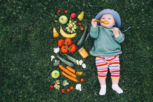 Bébé dans des vêtements colorés essayant la nourriture et le cadre de différents légumes de fruits frais sur l'herbe verte