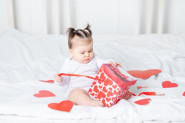 Bébé délie fort sur lit à la maison parmi les coeurs, concept de la saint-valentin