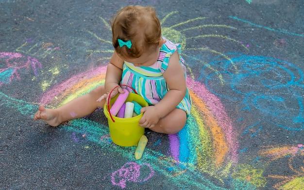 Bébé dessine un arc-en-ciel sur le trottoir avec de la craie. mise au point sélective. nature.