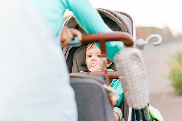 Bébé de dix mois mangeant une collation sur la poussette au coucher du soleil
