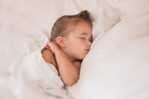 Bébé dort sur des draps blancs