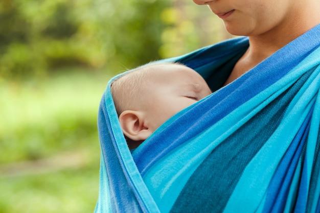 Bébé dort en écharpe, visage en gros plan