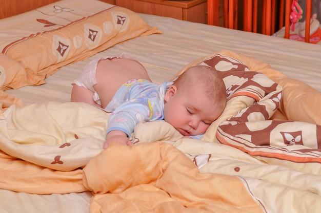 Le bébé dort sur le lit, couché sur le ventre.