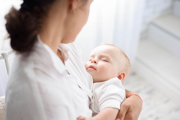Bébé dort sur la poitrine de la mère. jeune maman câlin bébé