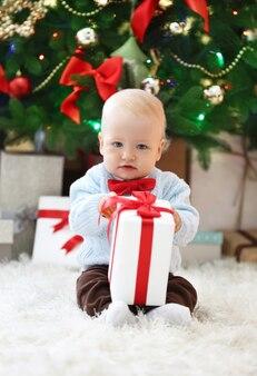 Bébé drôle avec boîte-cadeau et arbre de noël