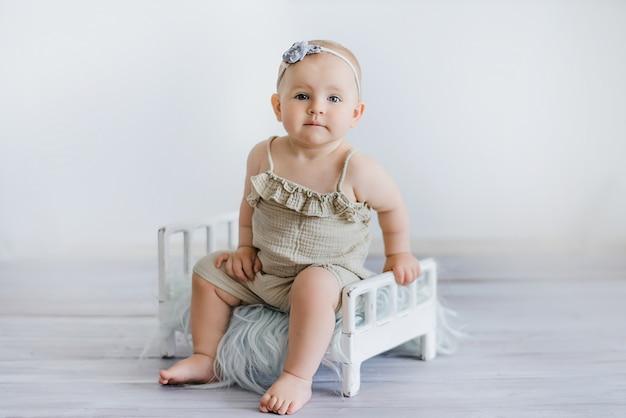 Bébé drôle sur le lit dans la chambre des enfants. carte de voeux. félicitations pour la fête des mères. mignonne petite fille de 9 mois assise et rampant. séance de garde