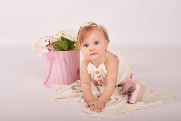 Bébé drôle mignon avec des fleurs. mignonne petite fille.