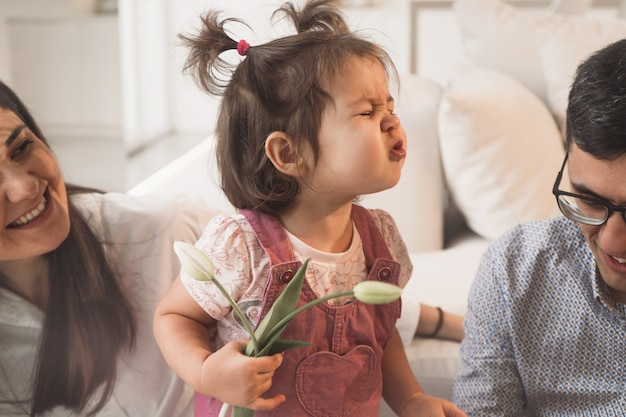 Bébé drôle rides nez. fille tenant une tulipe. photo de famille chaleureuse.
