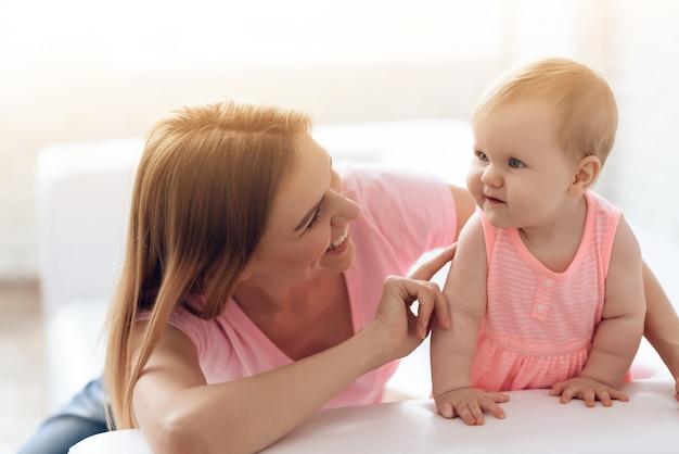Bébé embrassant avec joyeuse jeune mère souriante