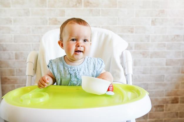 Bébé enfant mange avec cuillère dans la cuisine ensoleillée.