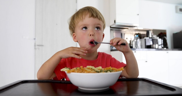 Bébé enfant mange des spaghettis à la maison dans le salon