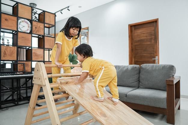 Le bébé escalade un jouet triangle pikler accompagné d'une soeur dans le salon