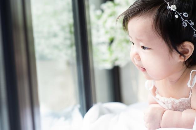 Le bébé est allongé et sourit en regardant par la fenêtre