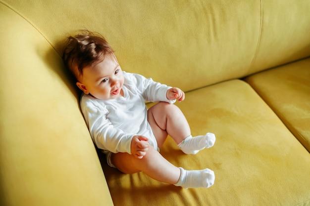 Bébé est assis sur le canapé jaune à la maison adorable espace copie bébé fille