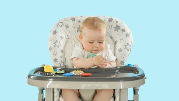 Le bébé est assis sur une chaise haute, jouant avec des jouets
