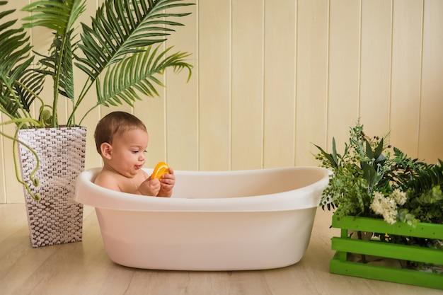 Le bébé est assis dans la baignoire et tient une orange sur un mur en bois