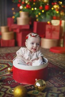 Le bébé est assis dans une boîte avec des boules de noël.
