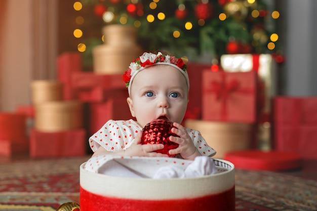 Le bébé est assis dans une boîte cadeau rouge avec une boule de noël ouverte