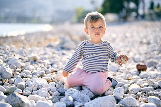 Bébé est assis à genoux sur une plage de galets et tient un caillou à la main