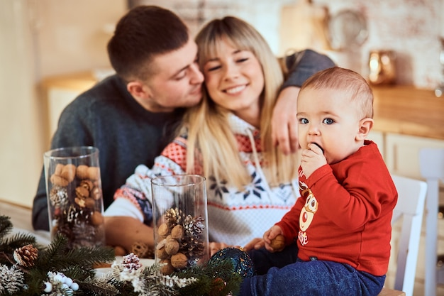 Bébé est assis à table, ses parents se font un câlin