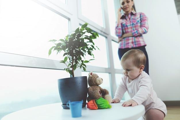 Le bébé est sans surveillance pendant que la femme parle au téléphone