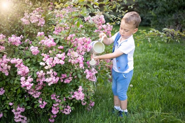 Bébé en étéa l'enfant rit tient un arrosoir arrose des fleurs en prenant soin de la nature