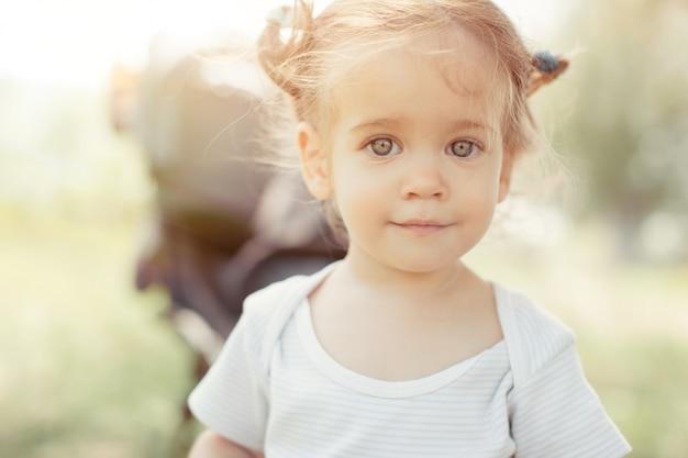Bébé fille debout près d'un landau