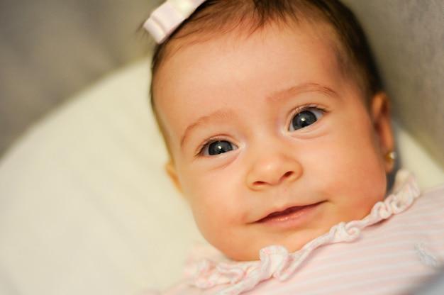 Bébé fille deux mois souriant à l'intérieur