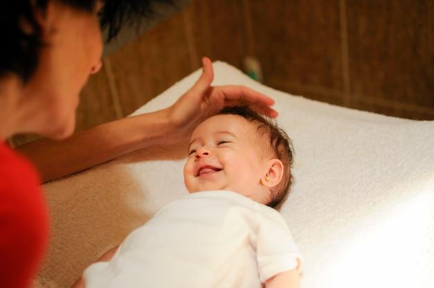 Bébé fille deux mois souriant à sa mère à la maison